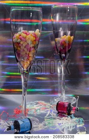 A Studio Photograph of Two Champagne Flutes Containing Sweets and Party Poppers Set Against a Silver Holographic Backdrop