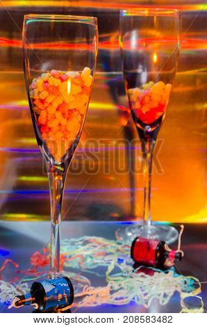 A Studio Photograph of Two Champagne Flutes Containing Sweets and Party Poppers Set Against an Orange Holographic Backdrop
