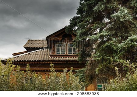 Old Russian wooden house among trees. The atmosphere of old Russian village. Ancient Russian wooden house from logs among old trees.