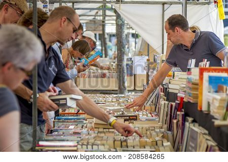 DORDRECHT NETHERLANDS - JULY 7 2013: Choosing and looking for second hand books at the annual book market held in the centre of Dordrecht. The market attracts 75000 visitors annually.