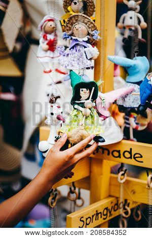 Wooden dolls dressed in different outfits. handmade wooden dolls hanging as a display. decorative dolls
