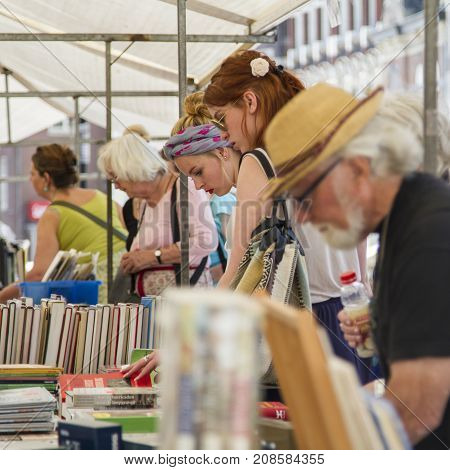 DORDRECHT NETHERLANDS - JULY 7 2013: People standing at a book stall deciding what to buy at the annual book market held in the centre of Dordrecht. The market attracts 75000 visitors annually.