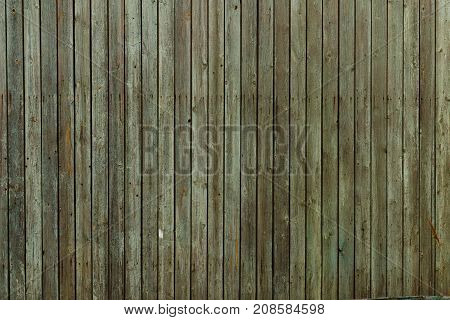 Old green boards. Old scraped green fence. Background of boards painted with green paint. Texture of green boards. Old green wood texture with natural patterns