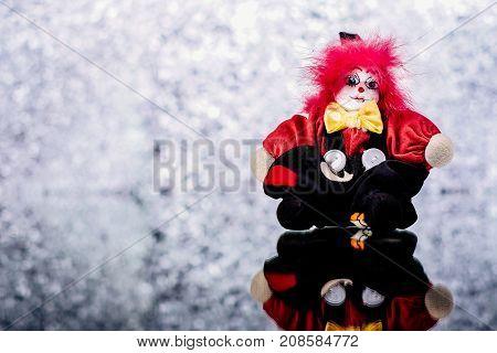 A creepy clown doll on silver shiny background
