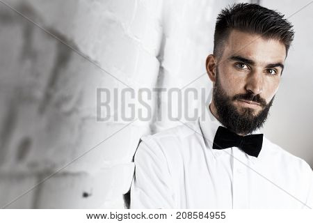 Portrait of serious bearded man wearing bow-tie and white shirt in front of white brick wall. Copyspace.