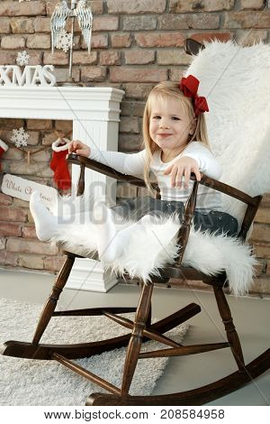 Lovely little girl swinging in rocking-chair, enjoying christmas celebration.