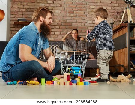 Father and son playing together at home on floor.