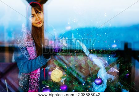 Young beautiful Asian woman in winter coat decorating Christmas tree at home.Young woman portrait shot trough the window.