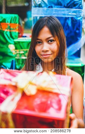 Tropical Christmas concept. Young woman in Santa Claus sledge with shiny colorful gifts