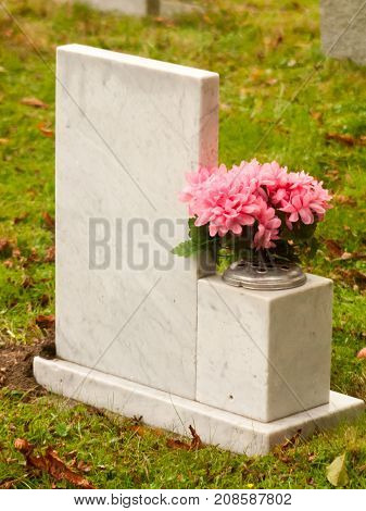 White Marble Gravestone From Behind With Pink Flowers Cemetery