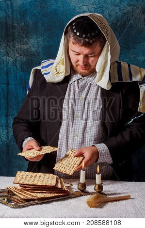 Jewish men is blessing on Matzah unleavened bread while another wearing a kippah scullcap reads the Haggadah traditional text during blessings for the Jewish holiday of Passover Seder meal.