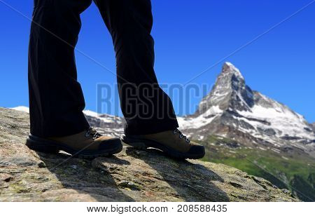 Mountain hiker on a trip in Pennine Alps, in the background Matterhorn peak, Switzerland.