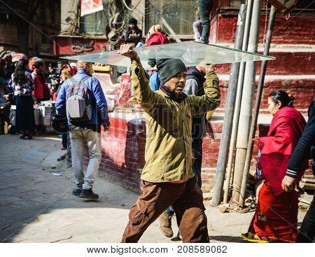 KATHMANDU, NEPAL - CIRCA JANUARY 2017: Nepali man carrying a sheet of glass on his head in Asan neighbourhood.