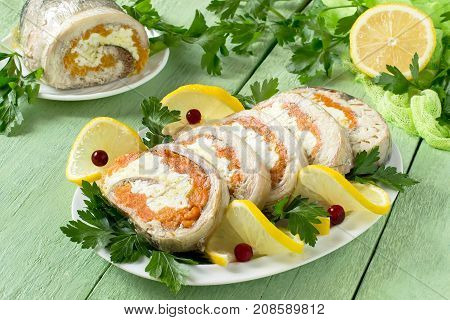 Homemade mackerel roll with carrots and eggs in gelatin. Cut slices of rolls are served with lemon cranberries and parsley. Festive snack. Mackerel roll lemon and parsley on green wooden table