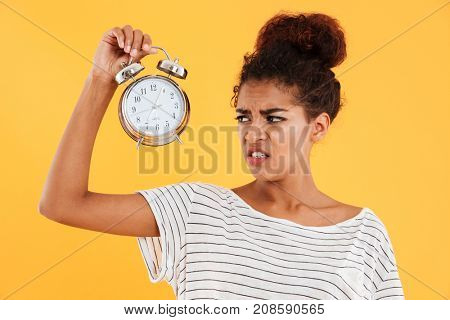 Displeased african woman holding alarm clock and looking on them over yellow background