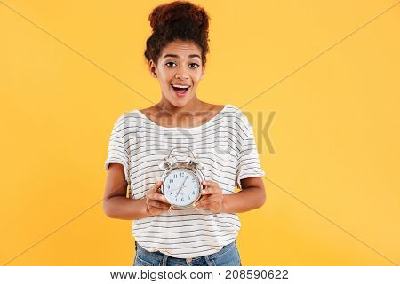 Happy african woman rejoice while holding alarm clock and looking at the camera over yellow background