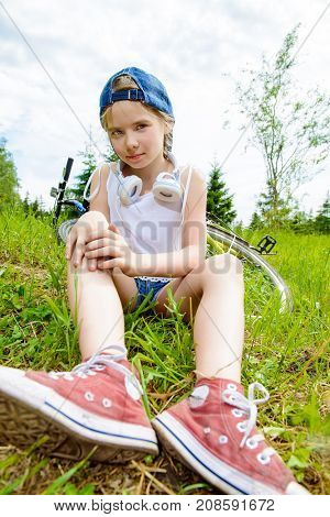 Cheerful girl resting on a green lawn after riding her bike. Happy summer holidays.