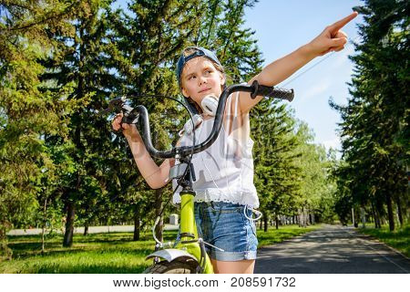 Cheerful girl is riding her bike in a summer park. Happy summer holidays.