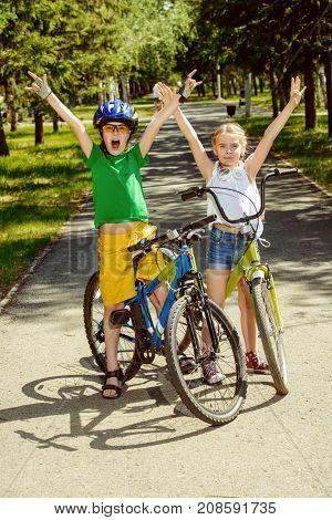 Two happy children riding their bikes. Happy summer holidays.
