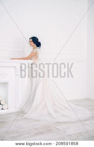 Portrait of a beautiful bride woman in elegant white wedding dress. Luxurious apartments.