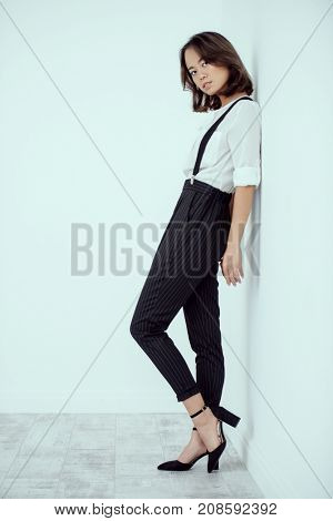 Young asian woman dressed in white shirt and classic trousers posing at studio. Business style in clothes. Fashion shot.