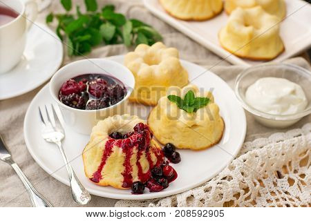 Baked sweet ricotta pudding cheesecake with sour cream and berry coulis