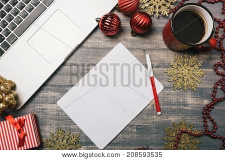 Office table desk, Flat lay. Workspace with laptop red cup on wooden background. Baubles garland tree ornaments gift box.