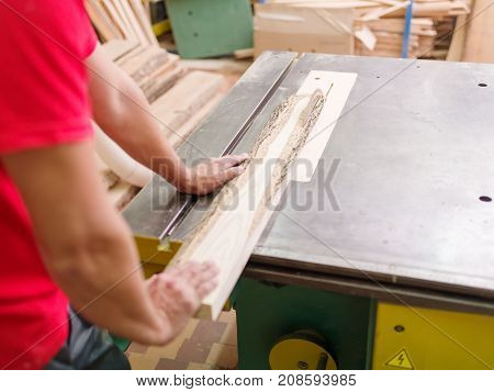 The carpenter saws a timber beam of wood on a circular saw close up in the working room