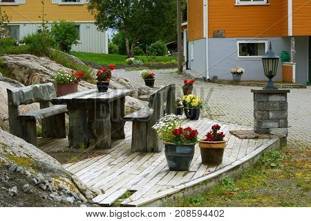 Rest area near the house with wooden table benches and flowers