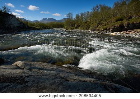 Landscape with turbulent river and blue sky