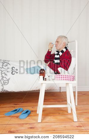 Senior sick man sitting in bed with medicines