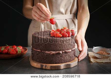 Woman decorating delicious chocolate cake with strawberries on table