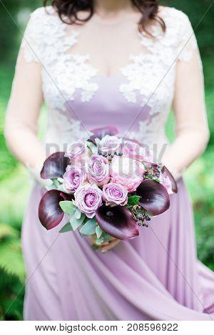 beautiful modern purple wedding bouquet in bride hands