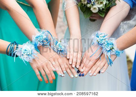 The bride and bridesmaids are showing beautiful flowers on their hands, outdoors