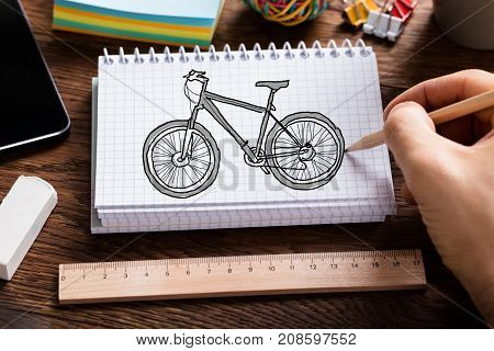 Close-up Of Person's Hand Drawing Cycle In Spiral Book With Ruler And Eraser On Table