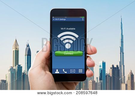 Close-up Of Hand Holding Smart Phone With Wi-fi Availability On Screen Against Building Skyscrapers