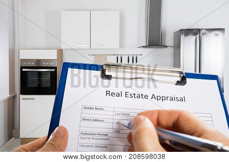 Close-up Of A Person's Hand Filling Real Estate Appraisal Form With Pen In Kitchen