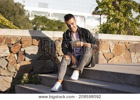 Happy young man reading on a tablet or listening to music on the stairs