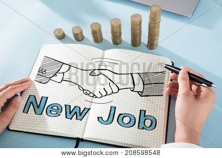 Person's Hand Drawing Handshake Icon With The Text New Job In Front Coin Stacks