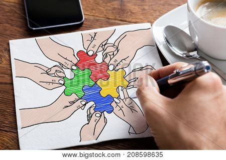 Close-up Of Person's Hand Drawing Colorful Jigsaw Puzzles On Paper On Desk