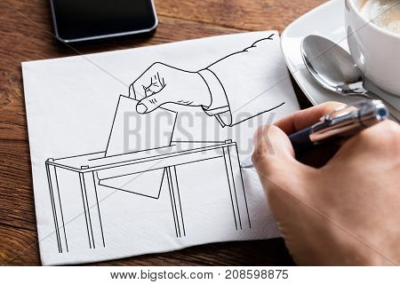Close-up Of Person's Hand Drawing Ballot Box On Paper