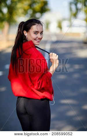 A sporty young woman in a red sweatshirt with headphones and a skipping rope. Young woman near the park in the fresh air in the autumn day. View from the back.