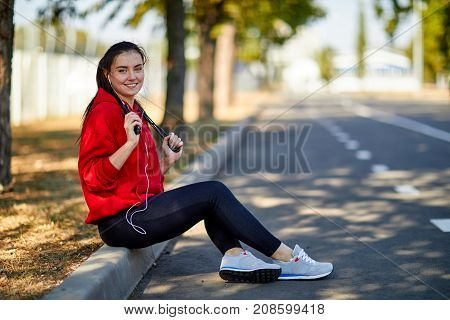 A young sports girl in a red sweatshirt listens to music with a rope in the fresh air in the park on the barge.