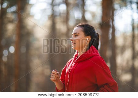 Young brunette athlete in a red sweatshirt is running around in headphones in an autumn forest. Close-up. In the profile.