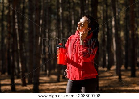 Young sporty woman in red sweatshirt. In the woods. Holds a red sport bottle. Close-up.