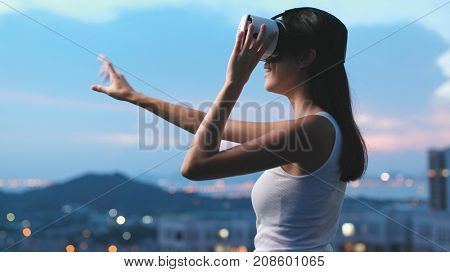 Woman watching with virtual reality device in the evening