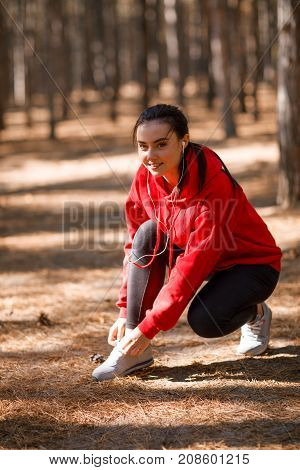 A girl in a red sweatshirt and headphones, tying shoelaces in the forest during training. Concept photo, close-up.