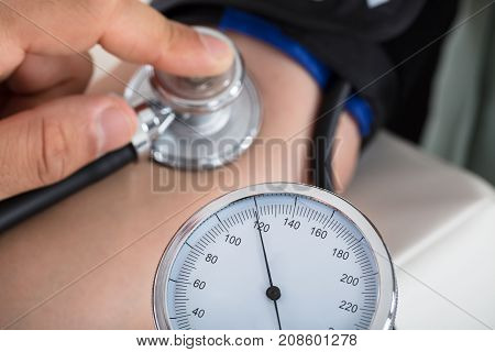 Close-up Of A Doctor's Hand Checking Blood Pressure Of Patient