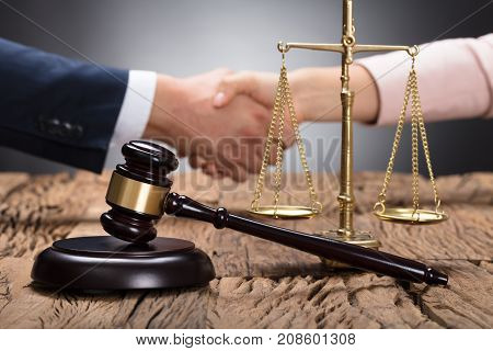 Close-up Of A Gavel And Scale On Wooden Desk In Front Of Businesspeople Shaking Hands