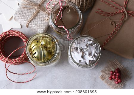 Christmas present wrapping supplies. High angle shot of three mason jars with gift tags, wood stars, and sleigh bells against a rustic white wood wall.